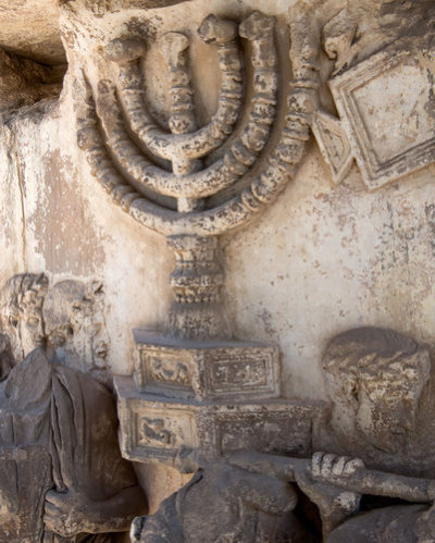 "The menorah, originally painted a rich yellow, on the Arch of Titus in the Roman Forum. Technology Identifies Lost Color at Roman Forum Historical sources describe the menorah looted by the Romans when they destroyed the Second Temple in Jerusalem in A.D. 70 as made of gold, as God instructed Moses in Exodus. So the recent discovery that a version of the menorah in a bas-relief on the first-century Arch of Titus in the Roman Forum was originally painted a rich yellow should not come as much of a surprise. But given that the image faded to the color of its underlying stone long ago — like so much else in and around the Forum — precise knowledge of its once-bright pigmentation comes as an exciting revelation to historians and archaeologists. ""The Bible said it was gold, but the monument, as it was seen for centuries, told us it was white,"" said Steven Fine, the director of the Arch of Titus Digital Restoration Project and a professor of Jewish history at Yeshiva University in New York, which is sponsoring the project. ""Isn't it cool to be that much closer to the viewers of the first and second century?"" The findings were made possible using noninvasive spectrometry readings carried out on the arch this month. ""The advantage of this method is that it doesn't harm the monument,"" said Cinzia Conti, the state archaeologist responsible for the arch. The monument is not only an important part of Rome's physical history but also ""very significant for the Jewish community,"" she said.  More here."