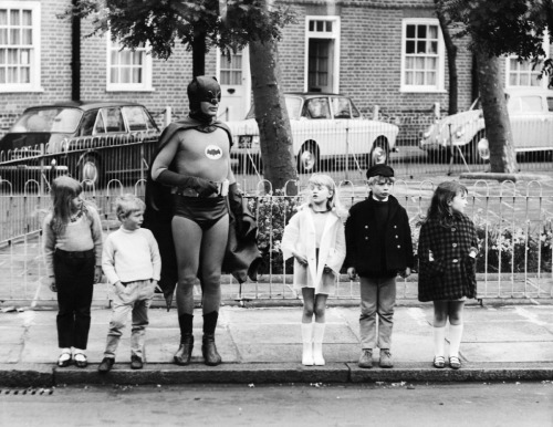 Adam West, dressed as Batman, making a road safety film with a group of child actors in Kensington, London, 1967