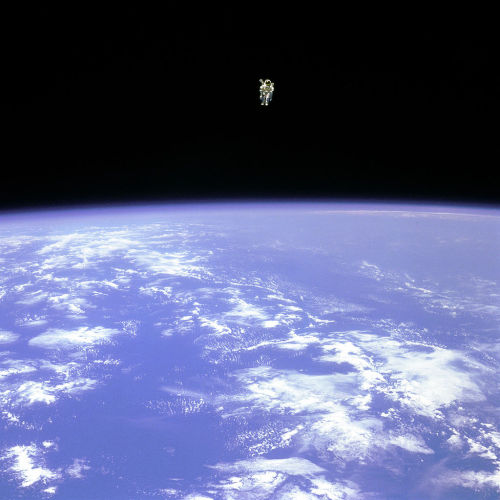 "Farthest Untethered Spacewalk  Mission Specialist Bruce McCandless II, is seen further away from the confines and safety of his ship than any previous astronaut has ever been. This space first was made possible by the Manned Manuevering Unit or MMU, a nitrogen jet propelled backpack. After a series of test maneuvers inside and above Challenger's payload bay, McCandless went ""free-flying"" to a distance of 320 feet away from the Orbiter. This stunning orbital panorama view shows McCandless out there amongst the black and blue of Earth and space. 12 February 1984"