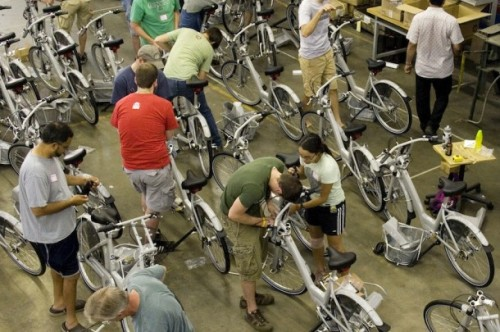 Kansas City Residents Build Their Bike Share Scheme One would not expect to find a bike share program in a car dominated metropolis like Kansas City, which has the highest ratio of highway lane miles to city population in the United States. A city that has a large number of highway miles can often lead to adverse health problems like obesity and diabetes. To top it all off Kansas City also has the lowest bike and transit ridership use in the nation as well, despite having one of the largest bike and nature trail networks in the country. BikeWalkKC, the regional bike advocacy group, is hoping to change the perception of car-dominated Kansas City to a healthier alternative of biking and public transportation. The group has a bold vision to have 75% of the city's residents living within bike/walk friendly areas by the year 2020. This vision will be accomplished through a combination of biking policies, public education, and research for future growth of bike networks. The group's regional efforts can be seen with the downtown metropolitan area enacting a number of complete street proposals and encouraging neighboring cities to implement bike friendly policies for future street improvements.  Kansas City's next infrastructural project will be to implement a Bike Share program across the city in conjunction with the future streetscape improvements. BikeWalkKC will run the bike share system and organized the bike build at donated warehouse space. Having the bike build will allow for both an enthusiastic public to actively invest in a future transportation system for their city and reduce costs for the assembly of the new bikes.  With over seventy-five volunteers in two events, the Bike Build is well under way to build the ninety new bicycles for Kansas City's B-Cycle program. Like an ant colony, BikeWalkKC strategically divided the vast number of volunteers into various stations based on their skill level. The general public can be amazing dedicated volunteers and quickly put to task the unpacking of ninety disassembled bikes onto the fabrication line. Once the last box was unpacked, various group leaders quickly integrated these volunteers into their part of the process to help foster further education. The next step of the assembly line was putting the various pieces of the bike such as the bike seat and basket onto the bike. Keeping with the spirit of sharing, BikeWalkKC developed a smart sharing system of the tools for the bike build that allowed quick transfers between groups. As the various components came together, another group concentrated on the fine tuning of the bikes to ensure that a high-quality bike was entering the new bike share program.  The most complicated and important piece of equipment is the embedded GPS locator for the bike. Each bike's unique key is linked to a GPS locator which tracks the bike's location throughout the city. This will allow BikeWalkKC to track where to service more bicycles and give insight into where more bicycle kiosks can be set up for future use.  With special support from local businesses Boulevard Brewery and Blue Cross Blue Shield of Kansas City, the Bike Build was a huge success for starting a new biking culture in Kansas City. The bikes will be ready for city-wide use on July 3, 2102 following the All-Star Baseball Series. The launch party will deliver get the bicycles to their docking stations ranging from the north River Market District to the south downtown areas of Union Station and Crown Center.  By Kyle Rogler, Studio 630 Via ThisBigCity