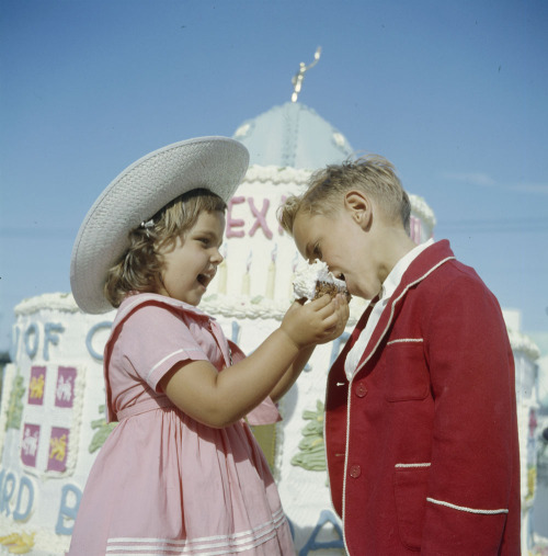 Happy Canada Day! Young girl feeding piece of cake to young boy during Dominion Day celebration, July 1st, 1961, Manitoba.  Photographer:Lund, Chris, 1923-1983 Source