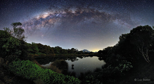 rwa42:  Milky Way Over Piton de l'Eau Image Credit & Copyright: Luc Perrot Explanation: Sometimes, if you wait long enough for a clear and moonless night, the stars will come out with a vengeance. One such occasion occurred earlier this month at the Piton de l'Eau on Reunion Island. In the foreground, surrounded by bushes and trees, lies a water filled volcanic crater serenely reflecting starlight. A careful inspection near the image center will locate Piton des Neiges, the highest peak on the island, situated several kilometers away. In the background, high above the lake, shines the light of hundreds of stars, most of which are within 100 light years, right in our stellar neighborhood. Far in the distance, arching majestically overhead, is the central band of our home Milky Way Galaxy, shining by the light of millions of stars each located typically thousands of light years away. The astrophotographer reports waiting for nearly two years for the sky and clouds to be just right to get the above shot.