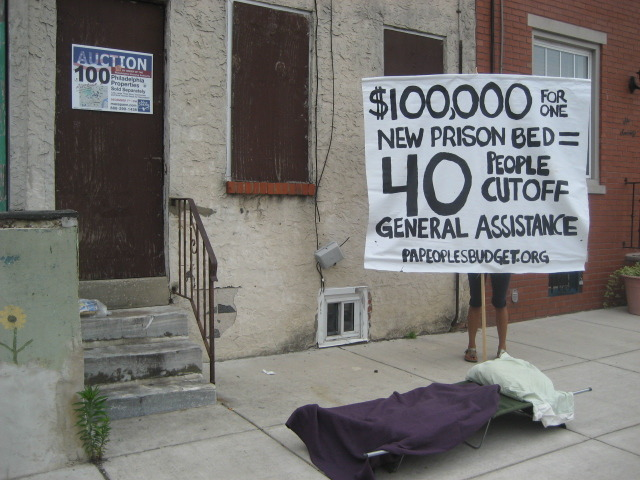 Picture This! The Real Cost of Prison Expansion in front of a foreclosed home in West Philly. Governor Corbett's proposed budget for 2012-2013 will eliminate funding for Pennsylvania's Homeowners Emergency Mortgage Assistance Program (HEMAP). For the past 28 years, the program has provided loans to homeowners who have fallen behind on their mortgage due to a job loss or other temporary hardship and are in danger of losing their home. Governor Corbett already slashed the program's budget to $2 million last year - such a drastic cut that the program announced it would not be able to continue operating. According to the Pennsylvania Housing Finance Agency, HEMAP has saved the homes of more than 46,000 Pennsylvanians from foreclosure. At the same time as Governor Corbett is taking away a critical safety net that helps keep Pennsylvanians in their homes, he is spending $685 million to build three new prisons and expand nine existing facilities. Instead of helping Pennsylvania residents maintain safe, stable homes for their families that will allow them to grow and succeed, Governor Corbett is choosing to invest in more unnecessary prison cells. Tell Governor Corbett and the PA legislature that we want homes, not prisons! For more on HEMAP's years of success in helping people stay in their homes, see: http://online.wsj.com/article/SB10001424052748704561004575013263982822140.html For more on Decarcerate PA's demand for a moratorium on prison construction, visit: www.decarceratepa.info