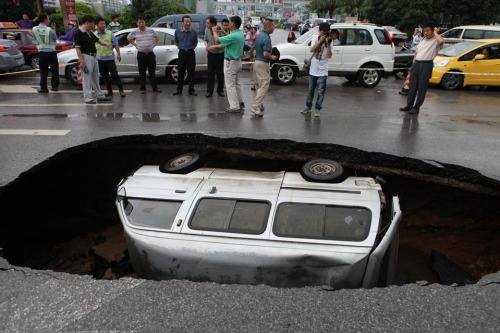 WSJ:  A van was trapped in a hole Friday in Guilin, China, where the road caved in after a rain.  photo credit:  Zuma Press (via WSJ)