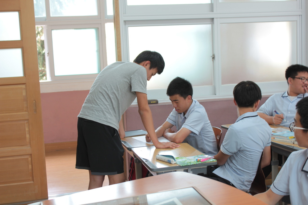 "Touching moment of the week: This week, our class participated in the Korean Students Speak project by writing and making signs to be posted later on the site. Tae-Hyun (seated), is one of the most quiet, socially awkward kids in the entire school. He lacks confidence in most everything he does and is painfully shy when it comes to speaking, even in Korean. As a result, most students groan in disappointment if he gets placed on their team for group games. With less than three minutes left to go before I announced we would be taking pictures, Tae-Hyun still had nothing written on his page. ""Joe"" (standing), one of the more popular kids in the 1st grade noticed this, left his buddies and walked over to his desk. He talked with Tae-Hyun for a few minutes and stayed with him until they had figured out something together. ""T-ara is forever"" read Tae-Hyun's sign after Joe fished out of Tae-Hyun what his favorite K-Pop band was."