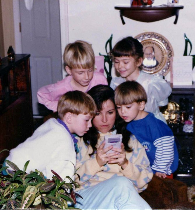 "tinycartridge:  ""My Mom helping me through a hard level in Super Mario Land on the day Nintendo Gameboy was released,"" uploaded by ZosaCloud (the boy in the blue shirt). I witnessed a similar scene with my wife recently, as she helped a young nephew run through a desert stage of New Super Mario Bros. on his DS Lite that I swear he's been stuck on for months. Why don't kids ever know that you need to hold down the run button the entire time? I wonder if, 20+ years from now, children will still rush to their parents and older relatives to get through difficult levels on the Nintendo HoloPro XL's new Mario game. Buy: New Super Mario Bros. 2 (August 19) Find: Nintendo DS/3DS release dates, discounts, & more See also: More handholding posts (our handheld gamer photo series) [Via ZosaCloud]"