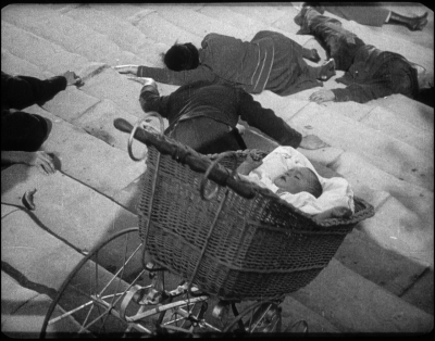 Battleship Potemkin (1925, Sergei Eisenstein; Cinematographers: Eduard Tisse, Vladimir Popov)  Life is destroyed in its infancy by tyrannous Russian tsarists in Sergei Eisenstein's seminal 1925 film, Battleship Potemkin.  When a mother is shot, and her baby plummets down a flight of steps, past piles of corpses, a trigger-happy militia, and the agonizing howls of trampled townspeople, the propaganda is front and center, blunt as a blackjack.  Here are the good guys.  Here are the bad guys.  Battleship Potemkin was Eisenstein's call to arms for the placated Russian public, urging them to organize under the banner of revolution, but the revolution was years past, and the solidarity of the Red Army – a convoluted wash of opposing factions. This famous Odessa Staircase sequence, referenced everywhere from DePalma's The Untouchables to a recent piece attributed to Banksy, is a classic bit of rhythm editing, building to a furious apex in which the carriage tips mid-motion, a tsarist soldier brings his weapon down on an unseen victim, and a peasant woman screams, her eye shot out, streaming blood.  The blood, unlike the hand-colored red flag on the titular ship, remains an oily void on the black and white celluloid canvas.  If Eisenstein's brutal Odessa montage force-feeds viewers a nasty bit of interpretive realism, his shots of the waving, bright red, revolutionary banner only perpetuated the fiction that the united, heroic compatriotism of 1905, the year in which the film takes place, was still alive and well two decades later, following the August Uprising and the death of V. I. Lenin. Esenstein's film remains a stunning cinematic achievement, and the Odessa Staircase scene one of the finest action set-pieces to emerge from the pre-sound era, but as a political text, Battleship Potemkin can't help but be swallowed up by the short-sighted folds of its own agitprop nostalgia.  There was, Esenstein suggests, a glorious moment for Russia and its people, when the revolution was young, powerful, and pure.  By 1925, that time had passed, and the patriotism of Battleship Potemkin was but a fleeting triumph for the divided Communist party, as it wrung out its oily flags, and prepared again for war, speeding blindly toward the bottom of the steps.
