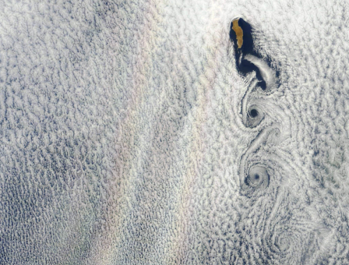 "joshsternberg:  Double rainbow seen from space. (Image: NASA image courtesy Jeff Schmaltz, LANCE MODIS Rapid Response) From NewScientist:  The glories are caused by diffraction of light back towards its source. The layer of stratocumulus clouds normally reflects a portion of solar energy into space and in this image the clouds are diffracting the sunlight back to the satellite splitting the light into its constituent colours. It has been suggested that enhancing the reflective property of stratocumulus clouds through geoengineering could help negate climate change. These glories look to us like the famous ""double rainbow all across the sky"" captured in Yosemite.  h/t Kristin Butler.  and triple hurricanes…"
