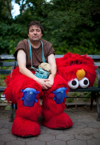"The man in the red Elmo costume was back to work in Central Park on Tuesday, but under the mask, he was not smiling. He was behind in tips he earns by posing for photographs with tourists. He said he had gotten a late start because he was not released from a psychiatric evaluation at a nearby hospital until midmorning.   And that's just the beginning of what is turning out to be a crazy story about that creepy Elmo from Times Square. (""Beneath a Ranting Elmo's Mask, a Man with a Disturbing Past"" via the NYT)"