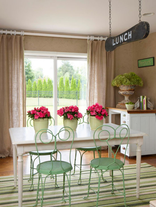 Mix & Match Repurpose outdoor furniture new life by bringing it indoors. Rustic materials, such as these wrought-iron cafe chairs and the wooden antique farmhouse table, complement each other perfectly and create a cozy dining area. Vintage signs hung from the ceiling and on the walls add undeniable cottage character and distinguish the space as an eatery.