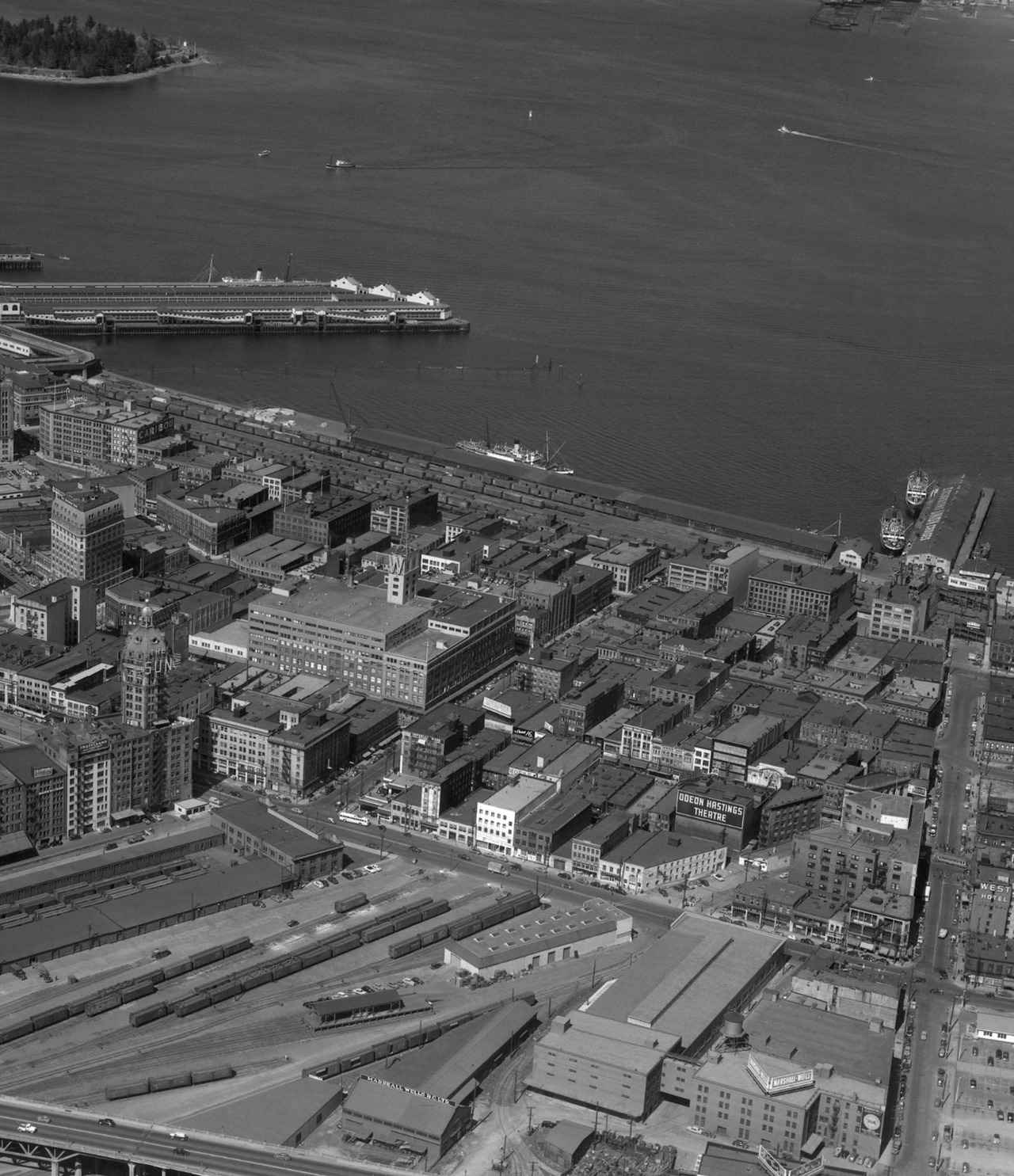 "Vancouver Aerial, 1951 In my routine scouring of the internet in search of old Vancouver photos, I came across a website filled with some amazing, high quality mid-century aerial shots of BC. The images are scans of photos taken by the website owner's father, who worked in the survey/drafting/mapping business from the late 1940s to the late 1960s. More photos are being added as they get scanned, and high quality prints are available for purchase.  This image is part of a 1951 photo of Vancouver north of the old Georgia Viaduct. It's worth looking at the large size and checking out what's changed and what remains. Here are some things that stuck out for me: The Woodward's ""W"" is still at the base of the mini-Eiffel Tower base. (The tower originally supported a bright search-light type beacon, which Ottawa made Woodward's shut down because the same lights were used at the airport, hence the giant ""W""). The Vancouver Sun was still housed in the Sun Tower. The previous tenant was a Seattle-based moving/storage company called Bekins, an ad for which can be seen on a building on the other side of Pender. Simpson's department store is in The Landing building (where Steamwork's restaurant now is) and the International Village site was still part of the rail yards. The building marked ""Odeon Hastings Theatre"" was originally the lavish second Pantages Theatre (and later the Beacon) built in 1917. That site is now the new, Arthur Erickson designed, Portland Hotel. And at the bottom left is the old Georgia Viaduct traversing the train yard and parking lots; that area has since been transformed with a soccer field, park, mall, Chinese garden, and condos.  Source: VintageAirPhotos.com"