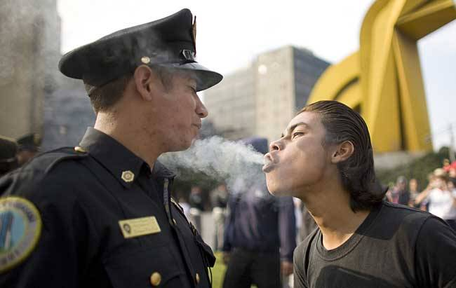 wild-soulchild:  faccc:  A protester blows marijuana smoke against the face of a police officer during a march to mark the 1968 Tlatelolco plaza 'massacre' in Mexico City  THAT COP JUST STOOD THERE BECAUSE HE WANTED CONTACT HIGH