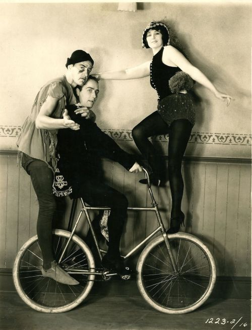 David Newell, Richard Arlen and Kay Francis ride a bike.