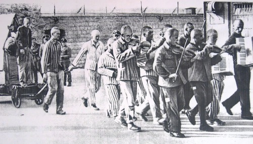 Hans Bonarewitz being led to his execution by the Mauthausen Concentration Camp orchestra following a failed escape attempt. He was locked in the crate for a week before finally being executed, 1942