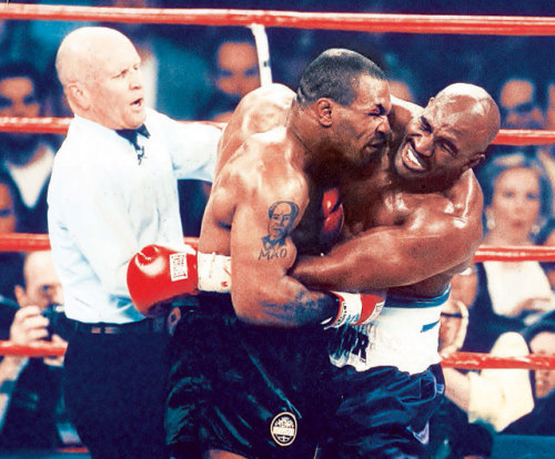 "siphotos:  Fifteen years ago today, Mike Tyson famously famously took a chunk of Evander Holyfield's ear during their fight in Las Vegas. Holyfield was awarded the winner after Tyson was disqualified for the biting incident. (V.J. Lovero/SI) GALLERY: Biting in Sports | Rare Photos of Mike TysonSI VAULT: Tyson drags his sport to new depths (7.7.97)  My friend and I went to an Allman Brothers concert the night of the fight. We ordered it on Pay Per View, and had the VCR set to record should we not get home in time after the show. On the way home, we got a call from my friend's brother, who had also ordered the fight. Him: ""Did you see the fight?"" Us: ""Not yet. What happened?"" Him: ""Well, I'll just say that it was very 'interesting,' and ended in the third round."" From the SI article above:  With less than a minute left in the round, and with no apparent provocation, Tyson got Holyfield in a clinch, rolled his head up and above Holyfield's shoulder and spit out his mouthpiece. What happened next was amazing, assuming you could believe your eyes. Tyson's mouth reached Holyfield's right ear and with a savagery that went well beyond what even his promoter could market, Tyson crunched down hard with his teeth and took a chunk right off. It was no saving grace that Tyson spit it out.  Someone posted the entire fight to YouTube:  The fight, er…the bite, was sick and twisted and bizarre. But, watch the aftermath. The entourages rushing the ring…Tyson's manager going on the defensive… Wild stuff."