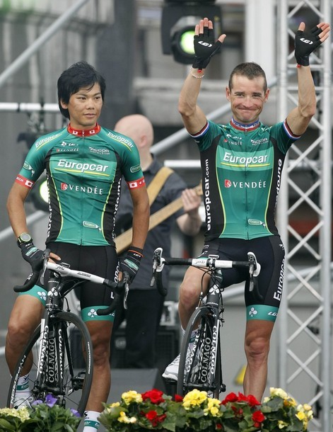 Team Europcar riders Thomas Voeckler of France and Yukiya Arashiro of Japan pose on the podium during the team presentation ahead of the start of the 99th Tour de France cycling race in Liege, June 28, 2012. (via Photo from Reuters Pictures)