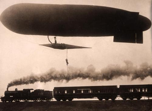 A zeppelin flying low over a steam locomotive. Below the airship is a man on a rope Nationaal Archief