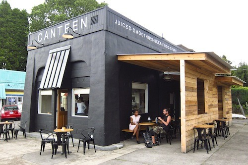 Canteen, an organic produce-fueled cafe/juice bar occupying the former Mojos Coffee Den space on SE Stark and 28th, launched mid-May with a full breakfast menu and coffee service, only to close days later due to a family emergency. After a short hiatus, the shop has re-opened, coffee-free and with shrunken service (i.e. lunch & dinner only). While the hours may be a bit unstable in the next few weeks, the hip little space is certainly worth a visit. The stark and modern surroundings—complete with modular shelving stocked with coconut water and loose leaf teas, a handmade wooden bar, and sleek metal magazine racks—give the cafe a Scandinavian flavor, while the outdoor seating provides chic coverage from the elements, a perfect place to grab a meal or afterwork pick-me-up.