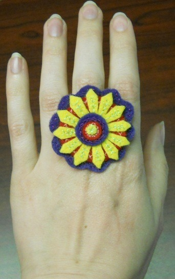 Flowery Frippery Adjustable hand Embroidered Felt Ring. Artist: Me - Amy Linehan This is being auctioned off through 'Eclectic Attic NL's facebook page in the Pump It Up auction. The Auction is to help raise money for a local young mans Insulin Pump (of whome I am friends and co-workers with). If your curious, click the link below! :D http://www.facebook.com/CommunityAuctionsFundraisers