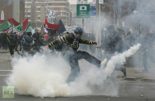 A student kicks a tear gas canister during an anti-government rally demanding changes in the public state education system in Santiago June 28, 2012