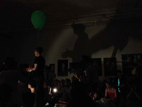 neil-gaiman:  From http://t.co/wuNVTZiG I have a green balloon. My shadow has wings. I am singing about murdering innocent people.  NEIL GAIMAN HAS WINGS. (And I am kind of photobombing his picture. Very pale girl is very pale, and wearing red.) (That was a grand night. A sweaty, wonderful, grand night.)