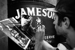 Hand painting a Jameson ad on Whythe ave on the side of the Kinfolk Bar