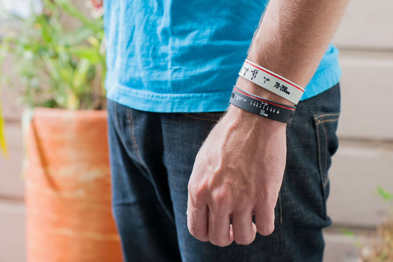 "photojojo:  The new pro Lens Bracelets look just like Canon and Nikon pro lenses … … so much so, your friends might think you took your lens apart! They come in 50mm and 70-200mm, but if you wanna go for a more minimal look, the original 24-70mm and 50mm are goodies, too. Whadda photo geek fantasy come true. New ""Canon"" and ""Nikon"" Pro Lens Bracelets!  I must have these bracelets o.O"