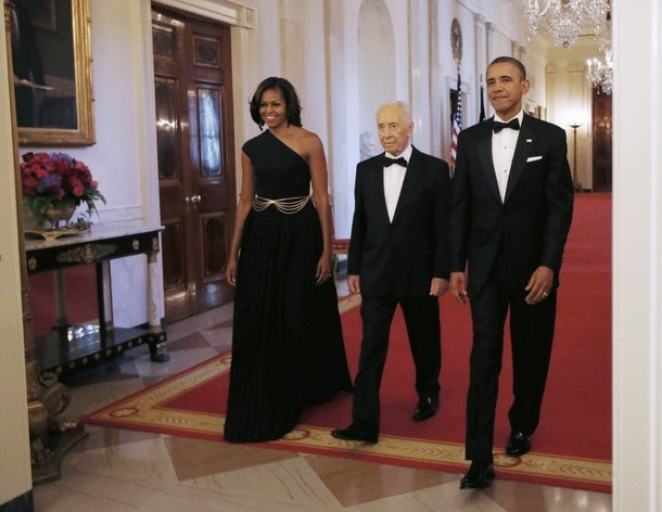 U.S. President Barack Obama and first lady Michelle Obama escort Israeli President Shimon Peres (C) into the East Room of the White House in Washington, June 13, 2012. President Obama awarded the Presidential Medal of Freedom to Peres during a ceremony at the White House on Wednesday. (via Photo from Reuters Pictures)