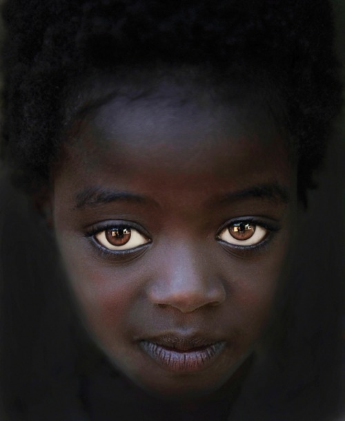 "harvestheart:  EYES OF THE OMO VALLEY ~ STEVE WALLACE, 58, PHYSICIAN, YUMA, AZ ""Visiting the tribes in Ethiopia's Omo Valley, I stopped at the Omo Child Home (omochild.org) in Jinka. I noticed this beautiful girl with big eyes looking out from a dark hallway. As I started taking pictures of her, she followed me with her eyes as I took photos from several angles. We did not have a common language, so I gave her no instruction.""TECH INFO: Nikon D3s with 24–70mm f/2.8 Nikkor at 62mm; 1/125 sec at f/2.8, ISO 400. Contrast and brightness adjusted in Adobe Camera Raw; eyes whitened in Photoshop CS5."