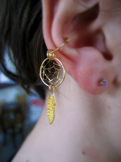 eclairs-for-models:  Review on Dream Catcher Ear Cuff What I love about it:  The dream catcher look is very in and so is the feathery boho look!  This ear cuff combines both in a perfect medley.  The metal isn't too hard, so you can change it to fit your ear!   Where to buy it: http://www.etsy.com/shop/Artistieke?ref=seller_info