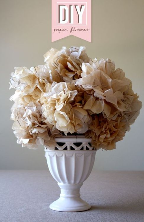 "fuckyeahweddingideas:  DIY Paper Flowers (via weddingchicks) Yellowed Sewing Patterns, Ruler, Scissors, 24-gauge floral wire, Skewers (optional)1. Stack 10 sheets of sewing pattens cut to 10″ square2. Fold 1-inch wide sections of the stack, working into an accordion fold3. and 4. Pinch, loop, and secure a 12-inch length of wire around the middle of the folded pieces. Round the edges using sharp scissors5. Carefully unfold the layers of paper, fanning into a round bloom6. A few gentle scrunches of the bloom will create the round ""hydrangea"" look that you want7. If you will be arranging the flowers in a big bouquet using floral foam, wrap the remaining wire around a skewer. You can wrap up to three blooms around one skewers"