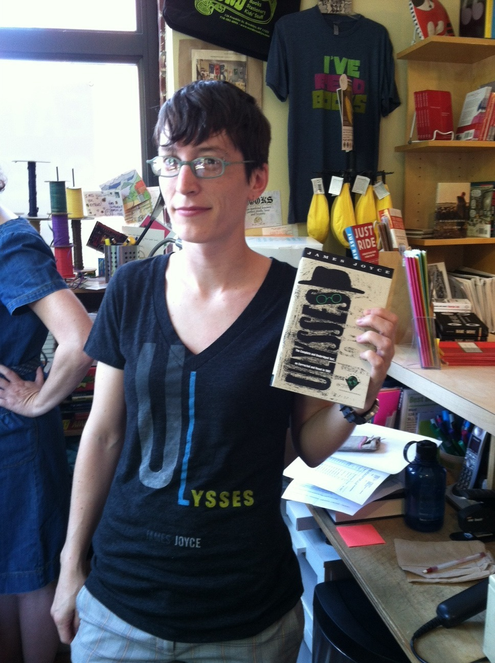 wordbrooklyn:  New manager Emily, caught in the middle of selling Ulysses to a customer WHILE WEARING A ULYSSES T-SHIRT. We think she'll do just fine.  NURD.