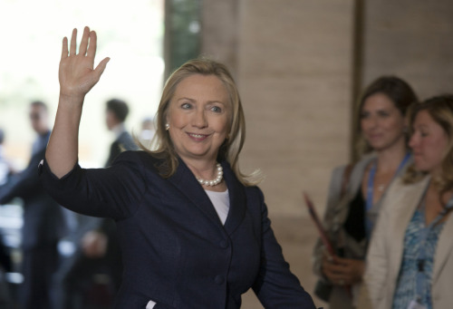 U.S. Secretary of State Hillary Rodham Clinton waves after arriving at the United Nations Office at Geneva, Switzerland June 30, 2012. [State Department photo by Eric Bridiers/ Public Domain]