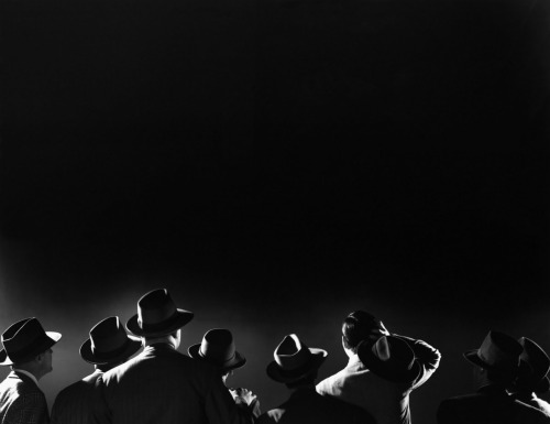 Men in hats look up at the night sky, ca. 1945 © Bettmann