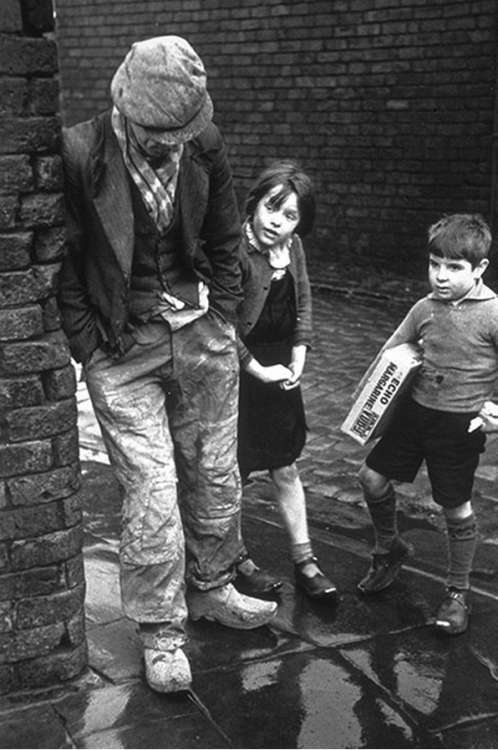 An unemployed man leaning against a wall with two children looking on, 1930s photo by Kurt Hutton