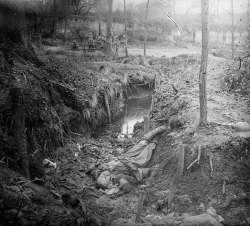talesofwar:  A German body in a small trench at Plessis-de-Roy. He was maybe killed by the French quad behind, but telling by their relaxed look, the combats must be away now. April 1918.