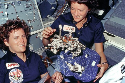 "Astronauts Kathryn D. Sullivan, left, and Sally K. Ride display a ""bag of worms."" The ""bag"" is a sleep restraint and the majority of the ""worms"" are springs and clips used with the sleep restraint in its normal application. Clamps, a bungee cord and velcro strips are other recognizable items in the ""bag. [A number of firsts in this image, and the mission, - the first American woman in space, the first American woman to walk in space and the first time the space shuttle carried more than one woman - ed]"