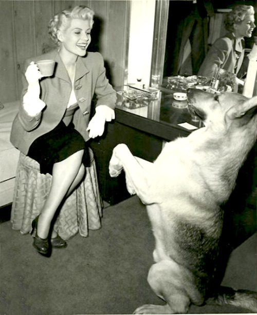 Rita Hayworth and her German Shepherd behind the scenes of The Lady From Shanghai in 1947, photo taken by Ned Scott.
