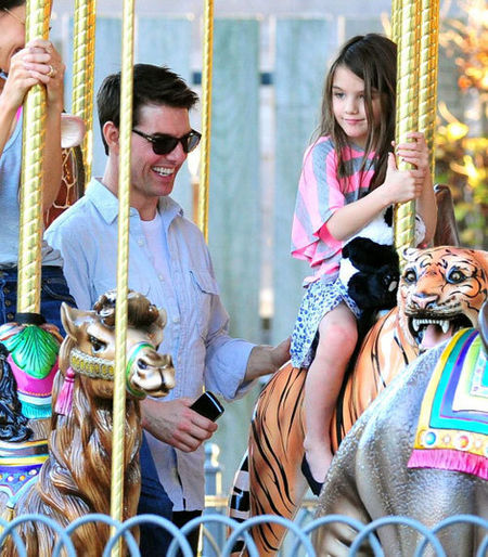 Tom Cruise com a filha Suri no carrossel.
