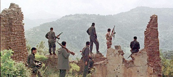 Al Qaeda men stand guard at their stronghold near Ouzou, Algeria.