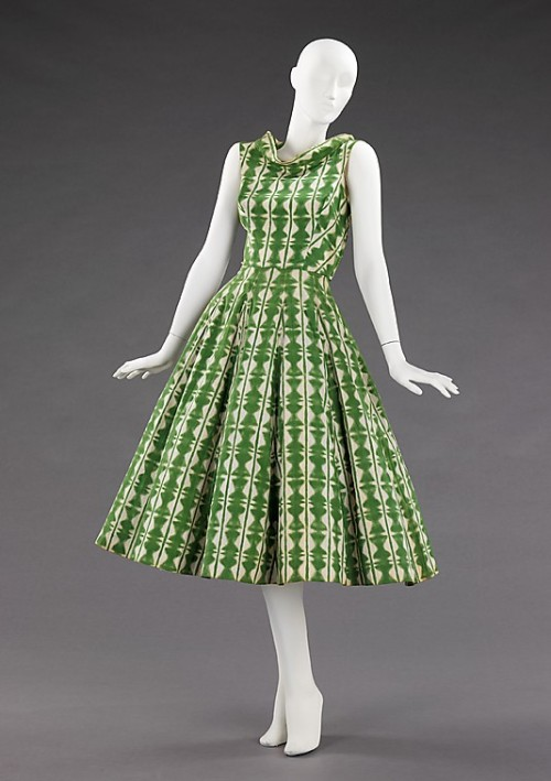 "Rice Bowl Dress | Carolyn Schnurer | c. 1952  For her ""Flight to Japan"" collection, Schnurer adapted elements of Japanese costumes and textiles, as well as architecture and decorative arts. In this example, the neckline, inspired by a reversed kimono, emphasizes the wearer's collar bones and delicately frames the face. The geometric textile pattern is inspired by sekkazome paper (meaning snow flower or snowflake dyeing), a technique in which mulberry paper is accordion pleated, folded into various patterns and dip dyed. The skirt, which is vertically boned, was inspired by Japanese oilcloth parasols. This effect creates a graceful A-line silhouette and was a practical alternative to the cumbersome crinoline petticoats prevalent in the early 1950s."