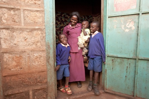 Lucy stands in the doorway of her home in Kenya with her three children, Daniel, James, and Mariam. Lucy and her husband are able to provide for their family and earn an income as farmers with the help of Kickstart pumps. Learn more at theadventureproject.org.