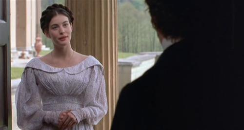 Onegin - Liv Tyler as Tatyana wearing a white printed cotton dress with wide neckline and round collar.