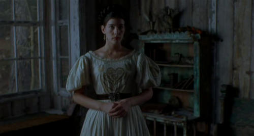 Onegin - Liv Tyler as Tatyana, wearing a white embroidered dress with lace-trimmed wide neckline and puffy sleeves, the waist chinched by a black belt with silver buckle.