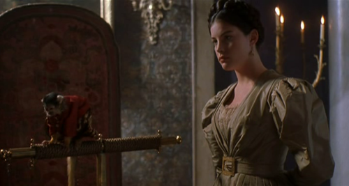 Onegin - Liv Tyler as Tatyana, wearing a sage taffeta dress with puffy sleeves. The neckline is embellished by a lace insert, while the waist is chinched by a taffeta belt with gold square buckle.
