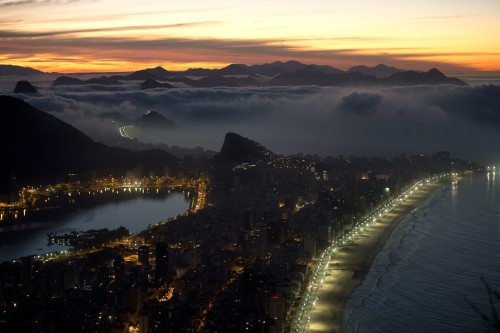 nonoo:  THE VIEW FROM IPANEMA: The sun rose over Ipanema and Copacabana beach in Rio de Janeiro on Friday. The World Heritage Committee will consider 36 sites, including Rio de Janeiro, for UNESCO's World Heritage List during its next meeting in St. Petersburg, Russia. (Christophe Simon/AFP/Getty Images)