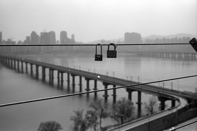 promises… on Flickr. The safety cables around the observation platform on the roof of Technomart in east Seoul are hung with padlocks placed there by young Korean couples as a symbol of their love. Some bear messages in Korean.  Jamsil Bridge and the Han River behind. Camera - Leica M3, with a Summicron 5cm f/2 DR lens.  Film - TMax400, processed in stock X-tol.
