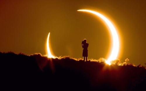 inothernews:  An observer is seen during a partial solar eclipse above Albuquerque, New Mexico.  (Photo: Colleen Pinski / Caters News via The Telegraph)