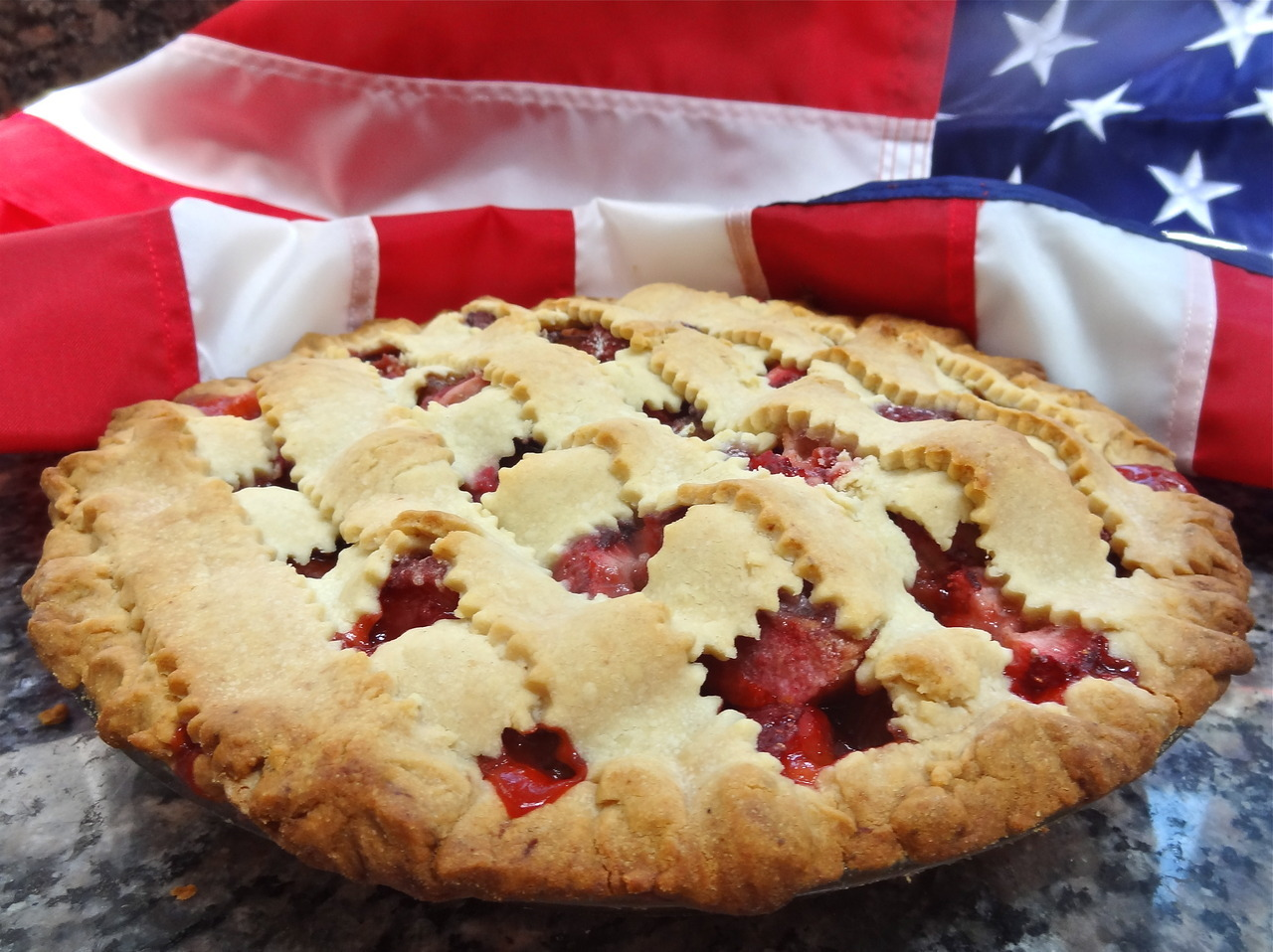 "Is there any food more ""American"" than pie? Okay, maybe. Hot dogs, hamburgers and stuff. Cole Slaw. Potato salad. And lots of others. Actually, none of the ones I mentioned were ""American"" at the start. Hot dogs, burgers and potato salad are German foods, Cole Slaw is Dutch and Pie began as British. No matter. They're American now, all terrific summer foods also. And all perfect for any Fourth of July celebration. So, when our local Hadassah decided that our biweekly Tea (for cancer patients and their caregivers at Stamford Hospital) should have a Fourth of July theme, I decided to bake a pie to give.  This one is red (sort of), white (beige crust/white sugar) and blue: a riff on Strawberry-Rhubarb Pie. It includes blackberries because I had some in the house and figured why not. You can leave out the blackberries and add more rhubarb and/or strawberries. Also, I used orange peel as flavor, but you can switch to lemon peel. And I used orange juice for the crust. First because orange goes really well with berries and rhubarb and also, my mother, a consummate pie baker, always told me that the liquid you use to make pie dough can be just about anything. She frequently used juice for fruit pie (the juice depended on the pie). Juice not only gives the crust more flavor, it helps the dough bake into a lovely brown color crust too. Strawberry-Rhubarb-Blackberry Pie dough: 2-1/2 cups all-purpose flour 3/4 teaspoon salt 1 teaspoon grated orange peel 1/2 cup unsalted butter 1/3 cup chilled vegetable shortening 4-5 tablespoons orange juice filling: 3 cups sliced (1/2-inch pieces) rhubarb, about one pound 2 cups strawberries cut in half 1 cup blackberries 2/3 cup sugar (or to taste) 1/4 teaspoon salt 5 tablespoons flour 1 teaspoon grated orange peel 1/4 teaspoon cinnamon 1 tablespoon butter   Combine the flour, salt and orange peel in a food processor. Add the butter and shortening in chunks and process on pulse about 24 times, until the mixture resembles coarse meal. Gradually add as much of the juice as is needed to make a soft, but not sticky dough. Cut the dough in half, flatten into disks and let the dough rest in the refrigerator for 30 minutes. Preheat oven to 375 degrees. Roll the dough into circles to fit a 9"" pie pan. Place one circle inside the pie pan. To make the filling, combine the rhubarb, strawberries, blackberries, sugar, salt, flour, orange peel and cinnamon. Add the filling to the pie pan. Cut the butter into chunks and place on top of the filling. Cut strips from the second dough circle and place them in a lattice design on top of the fruit. Seal the edges where the strips meet the bottom crust. Bake for 50-60 minutes or until golden brown. Makes one 9-inch pie"