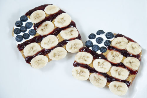 4th of July PB&J Banana Sandwiches  Open faced sandwiches on white bread with Smooth Operator peanut butter, raspberry jelly, bananas, blueberries, and fluff arranged into American flags. Conceived By Lee ZalbenPhotography By Andrea Hernandez